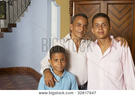 Hispanic father and sons hugging