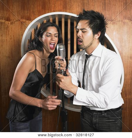 Multi-ethnic couple singing into microphone