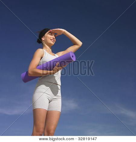 Mixed Race woman holding yoga mat