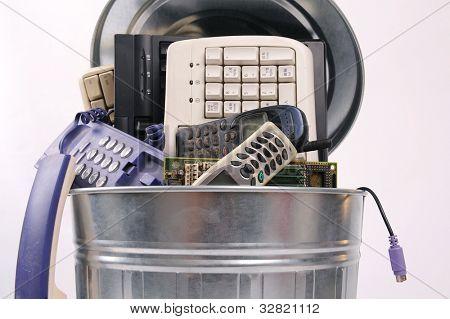 peças de computador diferente e telefone na lata de lixo