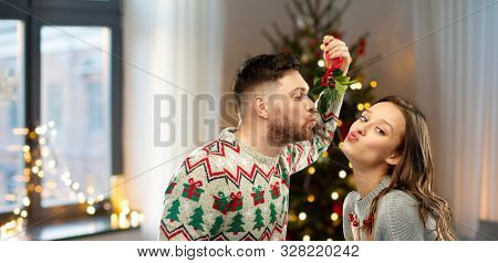 poster of people and holiday traditions concept - portrait of happy couple in ugly sweaters kissing under mist