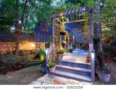 House exterior with porch walkay and lighting in the woods