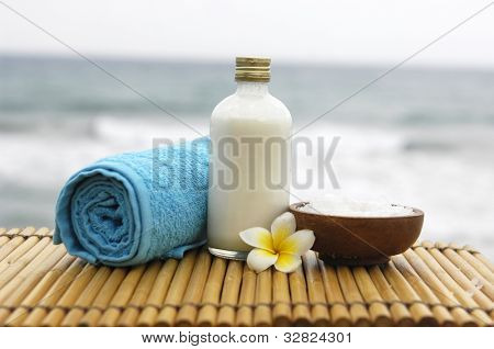 Zen concept �blue towel and salt in a glass with frangipani flower on mat