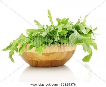 Fresh rucola salad or rocket lettuce leaves in wooden bowl isolated on white