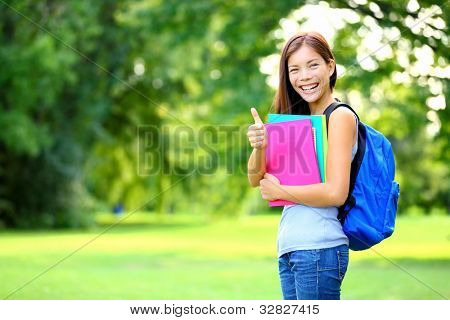 Student in park showing happy thumbs up success sign. Mixed race Asian Caucasian woman university student holding books outside.