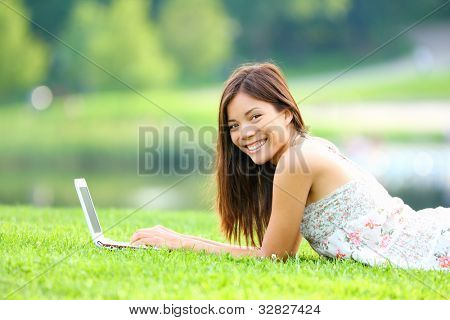 Girl in park on laptop. College student studying on laptop in summer or spring city park. Beautiful happy mixed race Caucasian / Asian chinese university student lying in the grass outside.