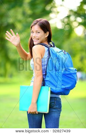 Woman student waving hello walking with school back in park smiling happy. Young female college or university student of mixed Asian / Caucasian race outside.