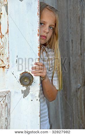girl peeking around old door