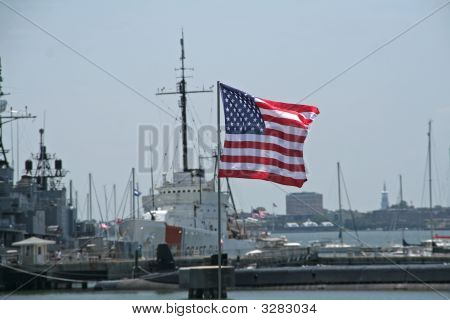American Flag In Focus Against Ships