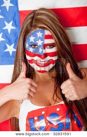 Feliz mujer estadounidense con la bandera de Estados Unidos pintada en el rostro con los pulgares para arriba