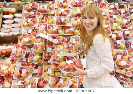 Happy girl wearing white shirt chooses packed apples in store; shallow depth of field