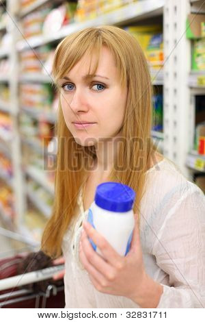 Blonde girl wearing white shirt keeps salt in store; shallow depth of field