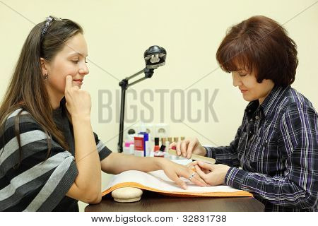 Manicurist makes manicure by nailfile for woman in beauty salon; focus on client