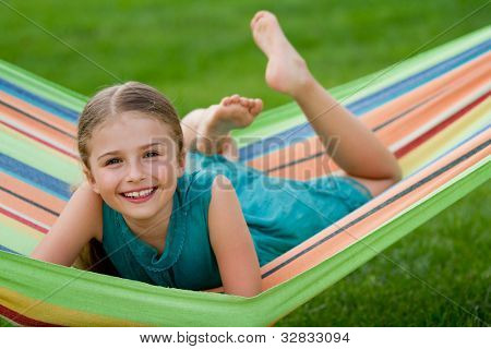 Happy summer - lovely girl in colorful hammock