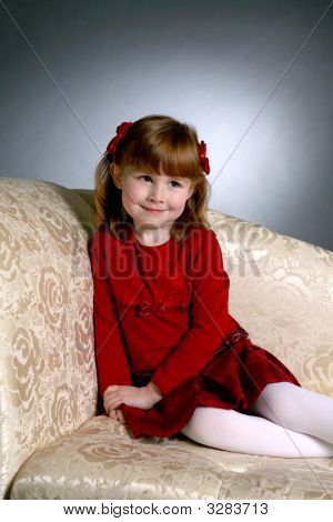 Cute Girl In Red On Couch