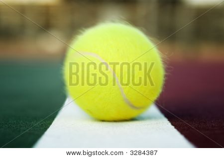 Tennis Ball Hitting The Baseline Of A Clay Court.