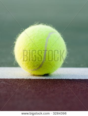 Yellow Ball Lands On Tennis Clay Court Base Line