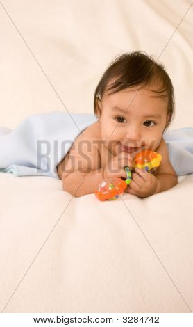 Ethnic Baby Boy With Toy Lying Down On Blanket