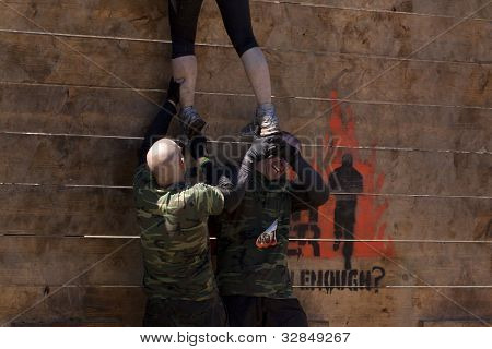 POCONO MANOR, PA - APR 29: An entrant gets help to get up and over the Berlin Walls obstacle at Tough Mudder on April 29, 2012 in Pocono Manor, PA.  The course is designed by British Special Forces.