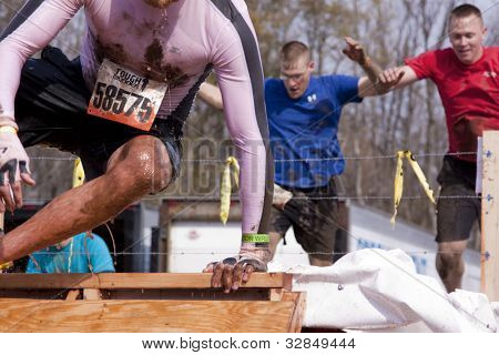 POCONO MANOR, PA - APR 28: A man emerges from a tank of water and ice while two men jump in at Tough Mudder on April 28, 2012 in Pocono Manor, PA. The course is designed by British Special Forces.
