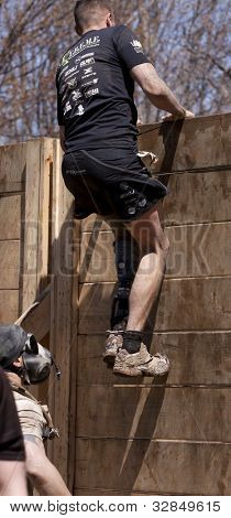 POCONO MANOR, PA - APR 29: A man pulls himself up and over the Berlin Walls obstacle at Tough Mudder on April 29, 2012 in Pocono Manor, PA.  The course is designed by British Special Forces.