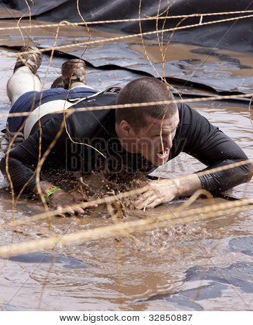 POCONO MANOR, PA - APR 28: A man crawls through water under electrified hanging wires at Tough Mudder on April 28, 2012 in Pocono Manor, PA. The course is designed by British Special Forces.