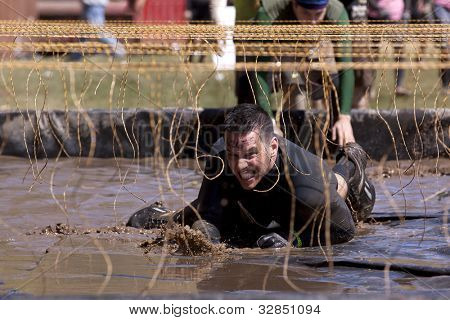 POCONO MANOR, PA - APR 29: A man crawls through water under electrified wires at Tough Mudder on April 29, 2012 in Pocono Manor, Pennsylvania. The course is designed by British Royal troops.