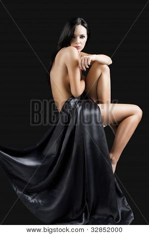 The Nude Cute Sexy Woman Over Black With Arm On The Knee