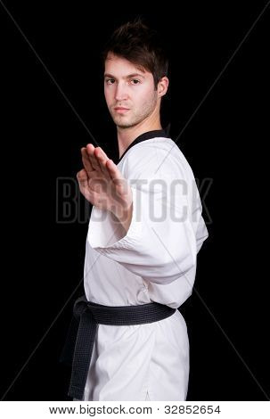 Young man in kimono make martial arts exercise on black