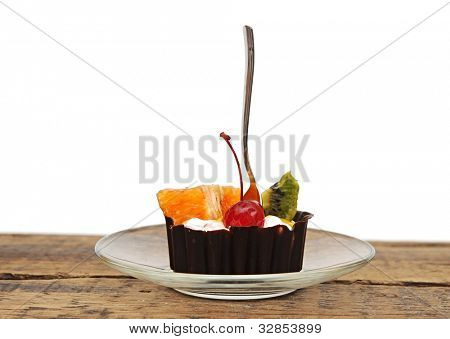 Chocolate cupcake with a cherry and tropical fruit on glass dish