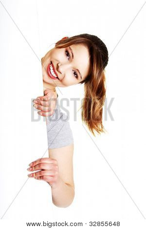 Beautiful young woman is holding blank whiteboard sign. Isolated on white background.