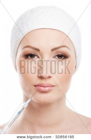 Beautiful woman gets injection in her face isolated on white