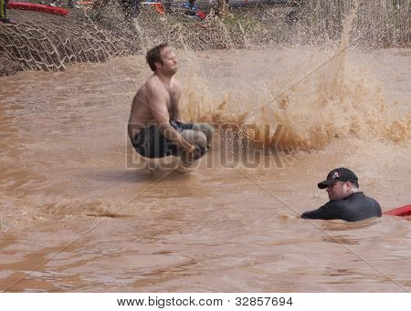POCONO MANOR, PA - APR 28: A man splashes into water from the Walk the Plank obstacle at Tough Mudder on April 28, 2012 in Pocono Manor, Pennsylvania. The course is designed by British Royal troops.