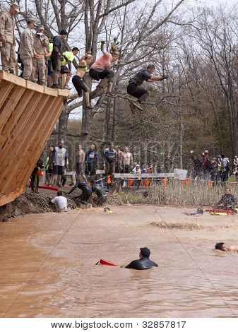 POCONO MANOR, PA - APR 28: Participants jump off the Walk the Plank obstacle into water at Tough Mudder on April 28, 2012 in Pocono Manor, Pennsylvania. The course is designed by British Royal troops.