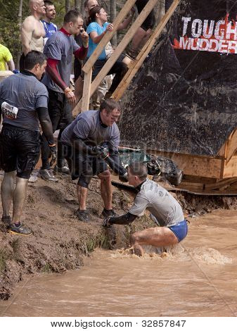 POCONO MANOR, PA - APR 28: Participants are helped from the water during the Tough Mudder event on April 28, 2012 in Pocono Manor, Pennsylvania. The course is designed by British Royal troops.