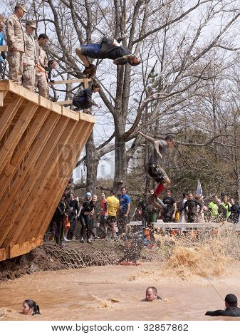 POCONO MANOR, PA - APR 28: A man does a flip off the Walk the Plank obstacle into water at Tough Mudder on April 28, 2012 in Pocono Manor, Pennsylvania. The course is designed by British Royal troops.