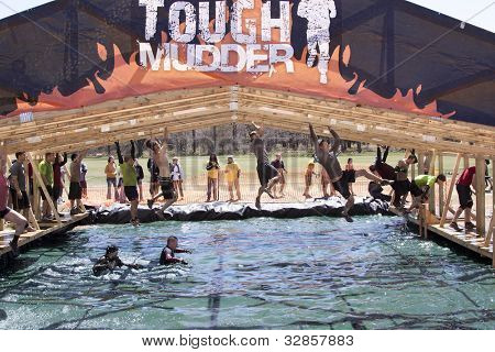 POCONO MANOR, PA - APR 29: Participants move hand-over-hand through an obstacle at Tough Mudder on April 29, 2012 in Pocono Manor, Pennsylvania. The course is designed by British Royal troops.
