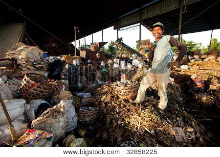 BALI, INDONESIA - APRIL 11: Poor people from Java island working in a scavenging at the dump on April 11, 2012 on Bali, Indonesia. Bali daily produced 10,000 cubic meters of waste.