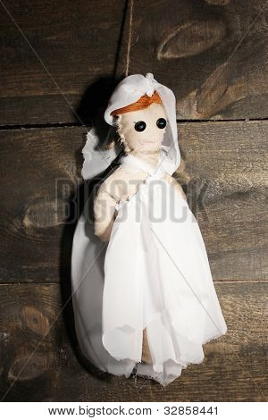 Hanged doll voodoo girl-bride  on wooden background