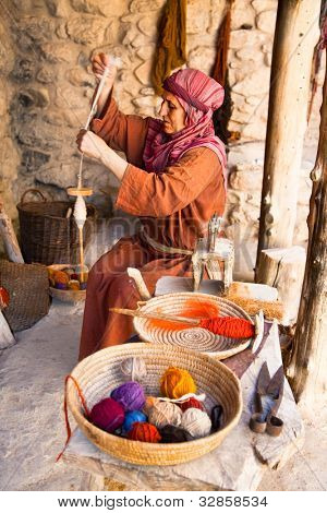 NAZARETH, ISRAEL - APRIL 24: Woman dressed as a first-century herder working old fashioned wool spinning wheel, a representation of life at the time of Jesus in Nazareth, Israel, Apr 24, 2012