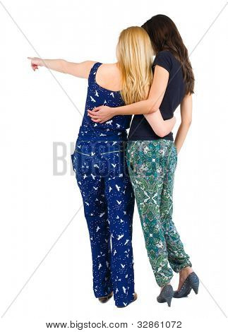 two young woman( back view )  (brunette and blonde) pointing at wall . beautiful girl friends  showing gesture.   Rear view people collection.  backside view of person.  Isolated over white background