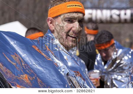POCONO MANOR, PA - APR 28: A man uses a foil wrap to get warm after finishing the Tough Mudder event on April 28, 2012 in Pocono Manor, Pennsylvania. The course is designed by British Royal troops.