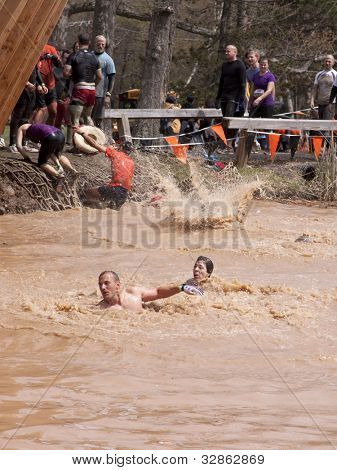 POCONO MANOR, PA - APR 28: Participants swim after jumping off an obstacle at Tough Mudder on April 28, 2012 in Pocono Manor, Pennsylvania. The course is designed by British Royal troops.