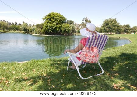 Woman Relaxing At A Park Lake
