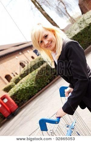 Ângulo visão de uma mulher loira atraente sorridente, empurrando um carrinho de compras através de um parque de estacionamento vazio