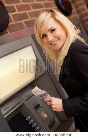Beautiful smiling blonde professional woman drawing cash at an exterior ATM