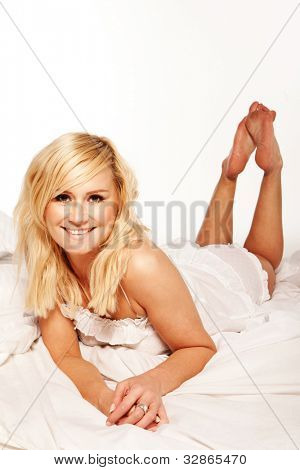 Pretty blonde laying on her stomach streched out on the bed with a smile