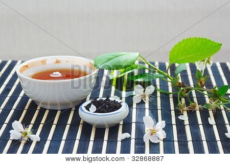 Cup of tea jar of tea leaves and cherry blossoms with leaves on bamboo table cloth