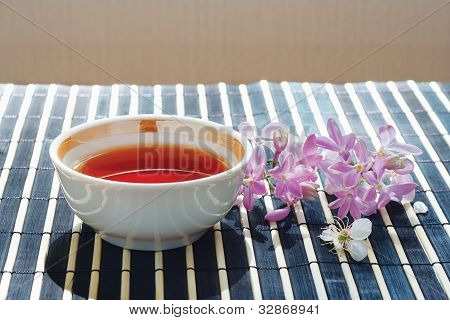 Cup of tea and cherry blossoms with lilac on bamboo table cloth