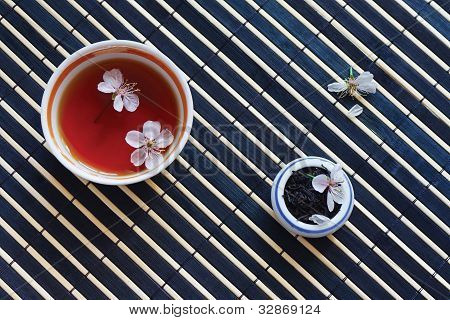 Cup of tea jar of tea leaves and cherry blossoms on bamboo table cloth